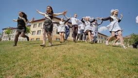 Los graduados felices de la escuela rusa aparecen de detrás la colina y el funcionamiento hacia felicidad almacen de metraje de vídeo