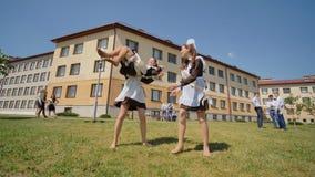 Los graduados rusos celebran el día escolar pasado Juego de los estudiantes en el claro verde metrajes