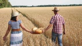 Los granjeros del hombre y de la mujer llevan adentro el pan de la cesta almacen de video