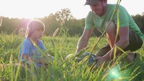 Los granjeros engendran e hijo que se prepara para comer la sandía en el campo de granja almacen de metraje de vídeo