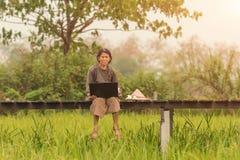 Los granjeros están utilizando los cuadernos que trabajan en campos del arroz fotos de archivo libres de regalías