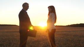Los granjeros hombre y mujer hicieron un trato hombre de negocios y empresaria que sacuden las manos en el resplandor de la puest almacen de metraje de vídeo