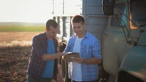 Los granjeros trabajan en el campo del trigo, comunican, miran la tableta Dos granjeros hablan en el campo, utilizan una tableta
