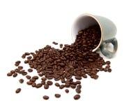 Los granos de café asados aromáticos vierten de una taza verde Imagen de archivo