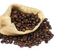 Los granos de café asados se derramaron en pila y en sacos de la arpillera Fotografía de archivo libre de regalías