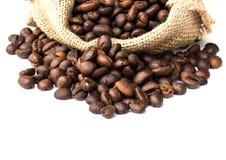 Los granos de café asados se derramaron en pila y en sacos de la arpillera Imagen de archivo
