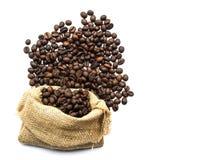 Los granos de café asados se derramaron en pila y en sacos de la arpillera Fotos de archivo libres de regalías