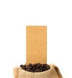 Los granos de café asados se derramaron en pila y en sacos de la arpillera Fotos de archivo