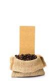 Los granos de café asados se derramaron en pila y en sacos de la arpillera Fotografía de archivo