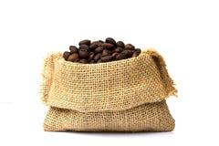 Los granos de café asados se derramaron en pila y en sacos de la arpillera Foto de archivo