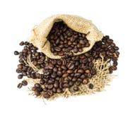 Los granos de café asados se derramaron en pila y en sacos de la arpillera Foto de archivo libre de regalías