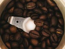 Los granos de café asados se muelen en una amoladora de café Foto de archivo libre de regalías
