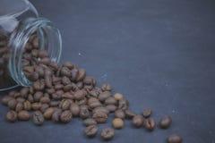 Los granos de café asados vertieron de un tarro de cristal colocación angular del objeto del café en el hormigón oscuro Visión ho fotos de archivo libres de regalías