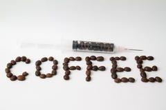 los granos de café asados y los granos de café llenaron la jeringuilla en la tabla Foto de archivo libre de regalías