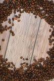 Los granos de café dispersaron en la opinión superior del fondo de madera con el plase para el texto Fotos de archivo