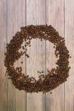 Los granos de café dispersaron en la opinión superior del fondo de madera con el plase para el texto Imagenes de archivo