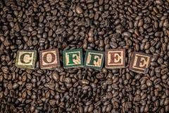 Los granos de café en granos de café de una caja de madera con de madera en el texto son café Imágenes de archivo libres de regalías