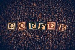 Los granos de café en granos de café de una caja de madera con de madera en el texto son café Foto de archivo