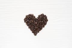 Los granos de café en una tabla en corazón forman el tiro en de madera blanco Imagenes de archivo