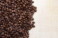 Los granos de café negros mienten en la tabla de madera ligera, imagen de fondo Lugar para el texto imagenes de archivo