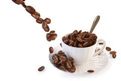 Los granos de café que caen en una taza Imagenes de archivo