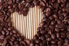 Los granos de café se presentan en una tabla en una paja o un soporte de madera imagen de archivo