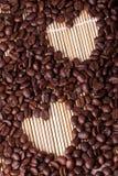 Los granos de café se presentan en una tabla en una paja o un soporte de madera fotografía de archivo