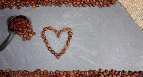 Los granos de café sueltan comercio justo con la cuchara y el corazón en el fondo del worktop de la cocina imagen de archivo