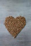 Los granos de los alforfones formaron en forma del corazón en fondo de madera Fotos de archivo libres de regalías
