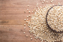 Los granos del arroz del mijo o del mijo en cuenco de madera pusieron la tabla de madera Fotos de archivo libres de regalías