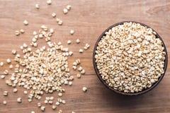 Los granos del arroz del mijo o del mijo en cuenco de madera pusieron la tabla de madera Imágenes de archivo libres de regalías