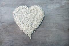 Los granos del arroz formaron en forma del corazón en fondo de madera Imágenes de archivo libres de regalías