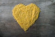 Los granos del mijo formaron en forma del corazón en fondo de madera Fotos de archivo
