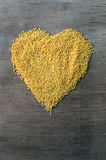 Los granos del mijo formaron en forma del corazón en fondo de madera Imagen de archivo