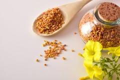 Los granos del polen de la abeja en tarro y cuchara de madera rematan Imágenes de archivo libres de regalías