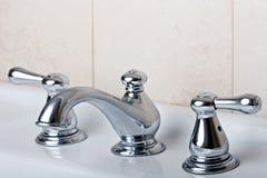 Los grifos de plata del golpecito del cuarto de baño del cromo moden estilo Imágenes de archivo libres de regalías