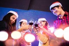 Los grupos de amigos son hombres asiáticos y las mujeres celebran la estación de la Navidad imagenes de archivo