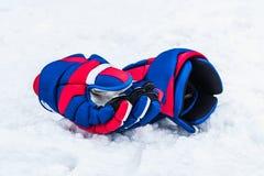 Los guantes coloreados del jugador de hockey mienten en la nieve Fotos de archivo libres de regalías