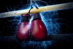 Los guantes de boxeo cuelgan en fondo de la luz de la electricidad fotografía de archivo