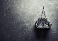 Los guantes de boxeo viejos cuelgan en clavo en la pared de la textura Imagen de archivo libre de regalías