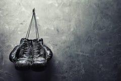 Los guantes de boxeo viejos cuelgan en clavo en la pared de la textura Imagenes de archivo
