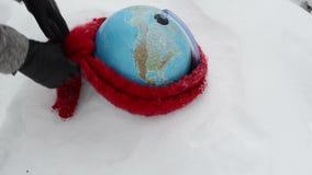 Los guantes de la mano del snowbank del invierno de la mentira de la esfera del globo de la tierra pusieron la bufanda almacen de metraje de vídeo