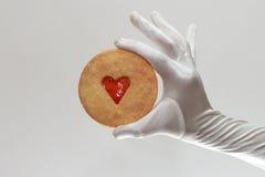 Los guantes de la mujer blanca que sostienen una galleta con el atasco en forma de corazón aislado en el fondo blanco Fotografía de archivo