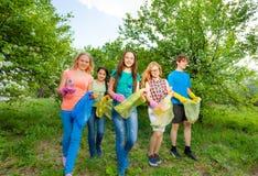 Los guantes del desgaste de los adolescentes y llevan el bolso de basura Foto de archivo libre de regalías