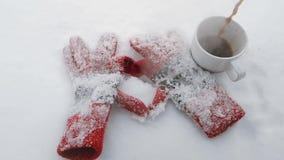 Los guantes del invierno hacen la forma de un corazón en una nieve con una taza de café caliente vídeo de la cámara lenta