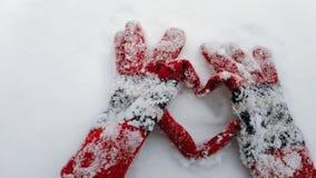 Los guantes del invierno hacen la forma de un corazón en una nieve vídeo de la cámara lenta Concepto para el día de San Valentín almacen de video
