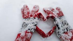 Los guantes del invierno hacen la forma de un corazón en una nieve vídeo de la cámara lenta Concepto para el día de San Valentín metrajes