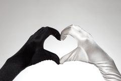 Los guantes en forma de corazón blancos y negros de las mujeres elegantes en el fondo blanco Imagenes de archivo