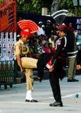 Los guardias del pakistaní que marchan y del indio en nacional uniforman en la ceremonia de bajar las banderas Lahore, Paquistán Foto de archivo libre de regalías