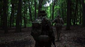 Los guerreros parciales de la guerrilla que caminan en bosque ambush llevar sus armas almacen de metraje de vídeo